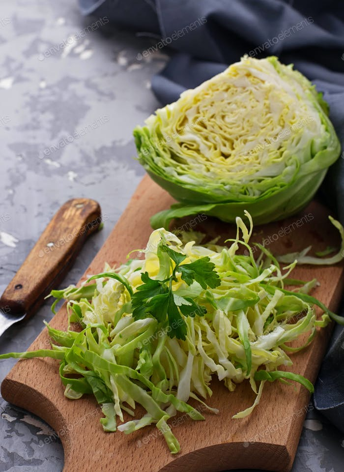 Raw cut cabbage on concrete background