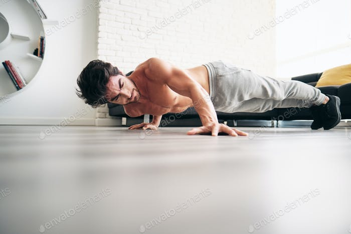 Adult Man Training Chest Muscles At Home With Archer Push-Ups