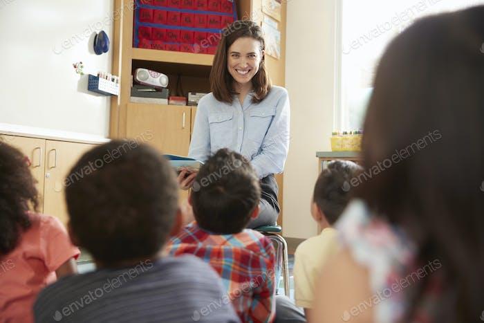 Elementary school kids listen to teacher, back view close up