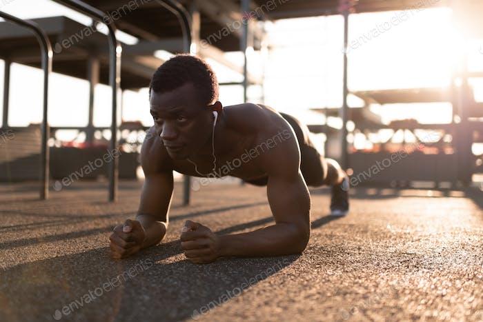 Sportive serious black man doing plank
