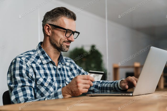 Pleased unshaven man using credit card while working with laptop
