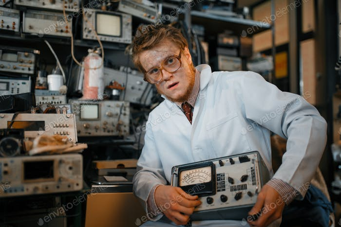 Crazy scientist holds electrical device in lab