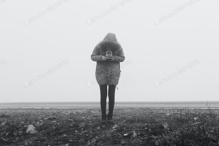 Woman with retro camera in a fog landscape