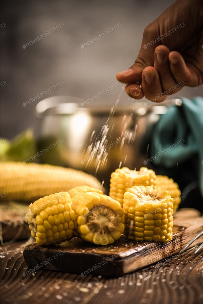 Hand salting hot cooked corn on the cob