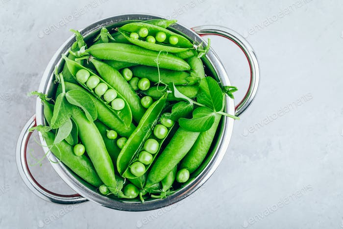 Fresh Raw Green Peas in a colander on gray stone background, top view