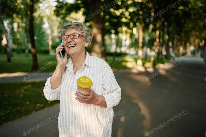 Pretty granny using mobile phone in summer park