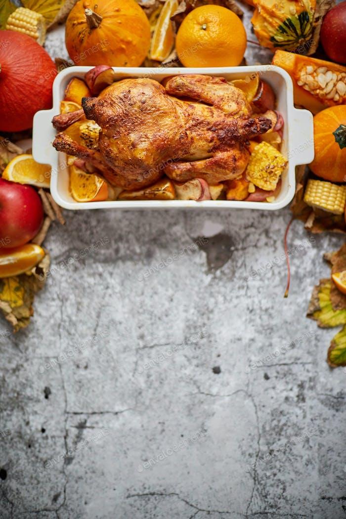 Festliches Huhn gebacken von Thanksgiving auf weißem Owen-Teller und einer Ernte von saisonalem Gemüse