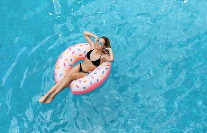Verführerische kaukasische Mädchen im Bikini schwimmen auf aufblasbaren Ring im Pool, Overhead-Ansicht. Leere Leerzeichen