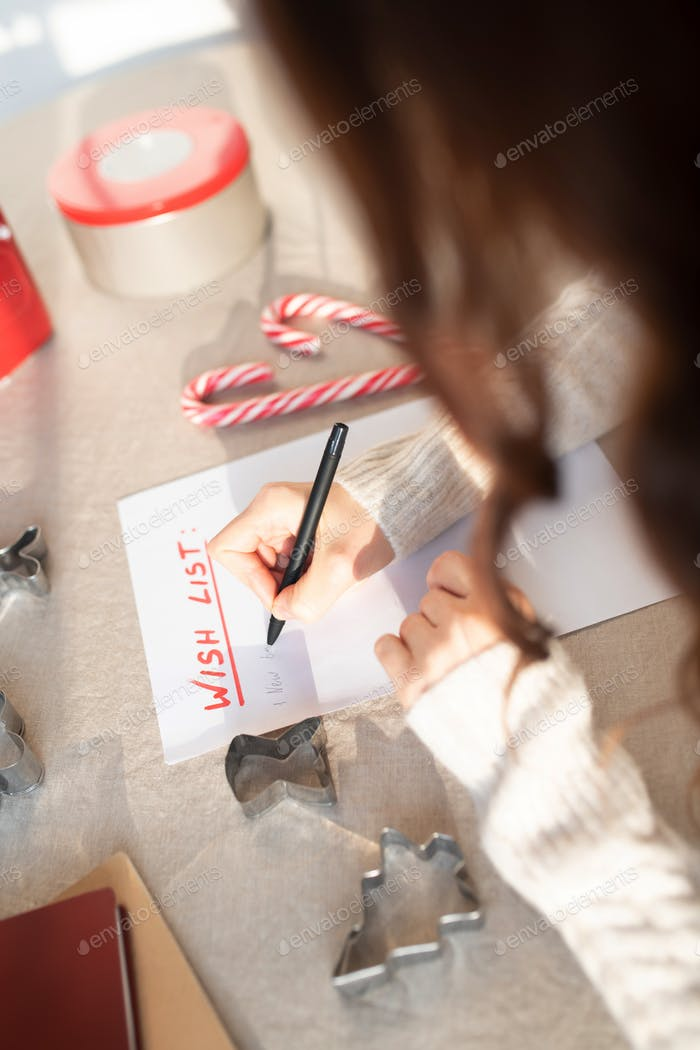 Woman writing a wish list for coming new year