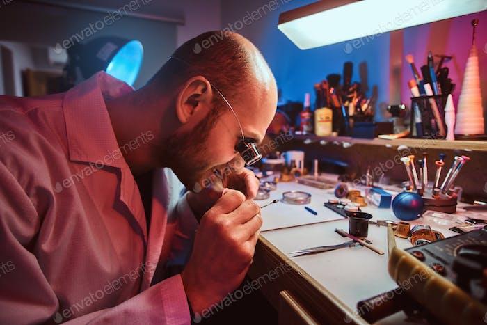 Fokussierter Meister arbeitet an der Uhr des Kunden in seiner Werkstatt.