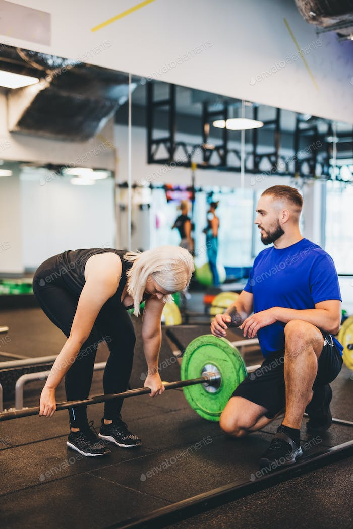 Personal trainer assisting woman lifting weights.