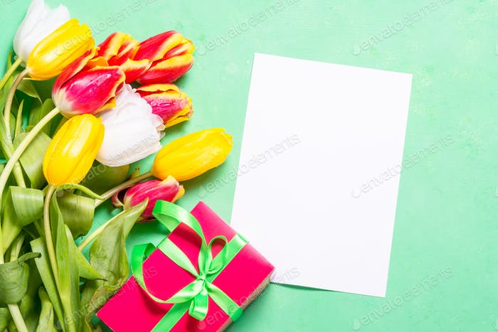 Flatlay flower holiday background. Tulips and paper.