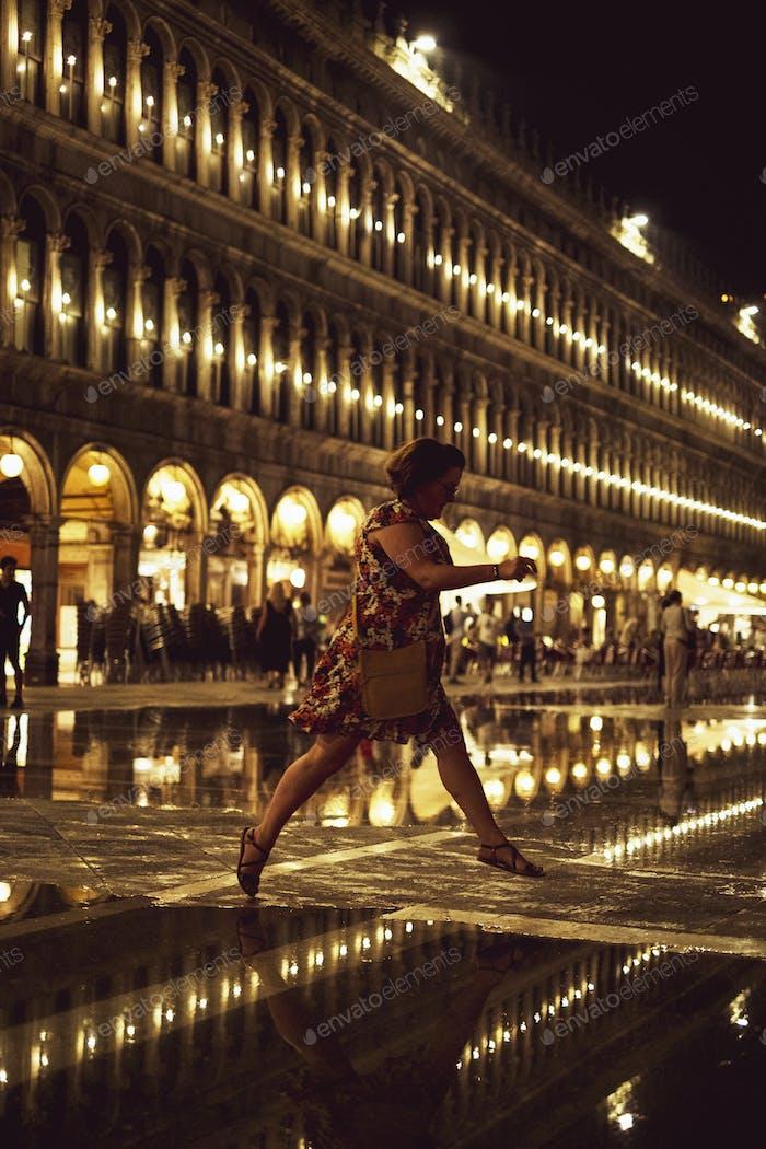 Frau, die nachts über einen beleuchteten Markusplatz in Venedig, Venetien, Italien, springt.