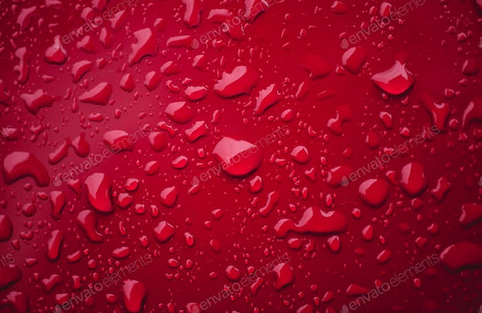 Water drops macro on a red surface