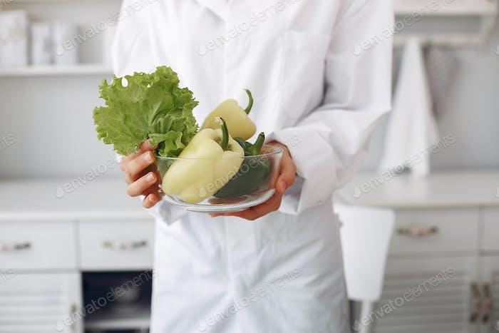 Arzt in einer Küche mit einem Gemüse