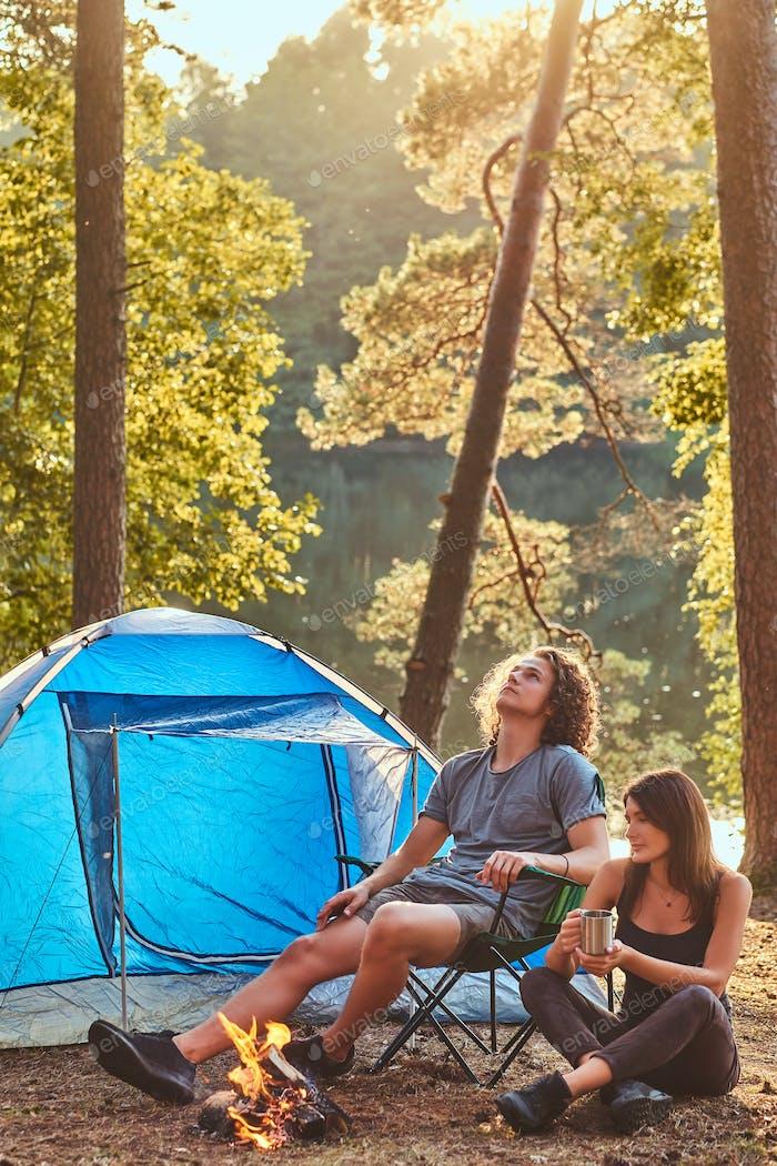 Junges Paar Wanderer sitzen wärmend in der Nähe eines Lagerfeuers im Lager im Wald an sonnigen Tag.