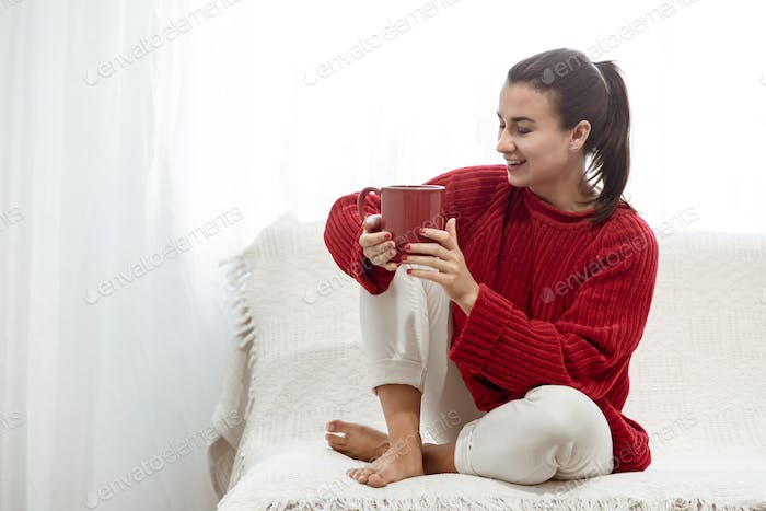 Young woman in a red sweater with a red cup at home on the couch.