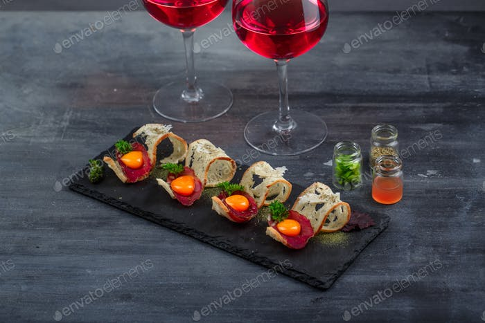 Appetizer with crusty bread, bresaola, cheese and yolk on stone background