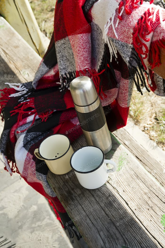 Thermos with hot tea on wooden table.