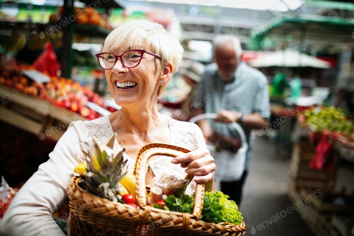 Mature woman buying vegetables at farmers market