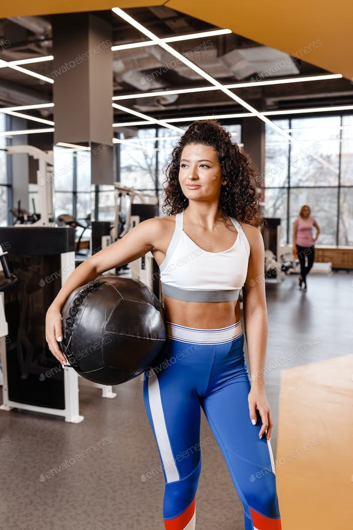 Slim girl with dark curly hair dressed in a sportswear is standing with heavy fitness ball in the