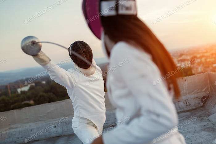 Two fencing athletes people fight on rooftop outdoors
