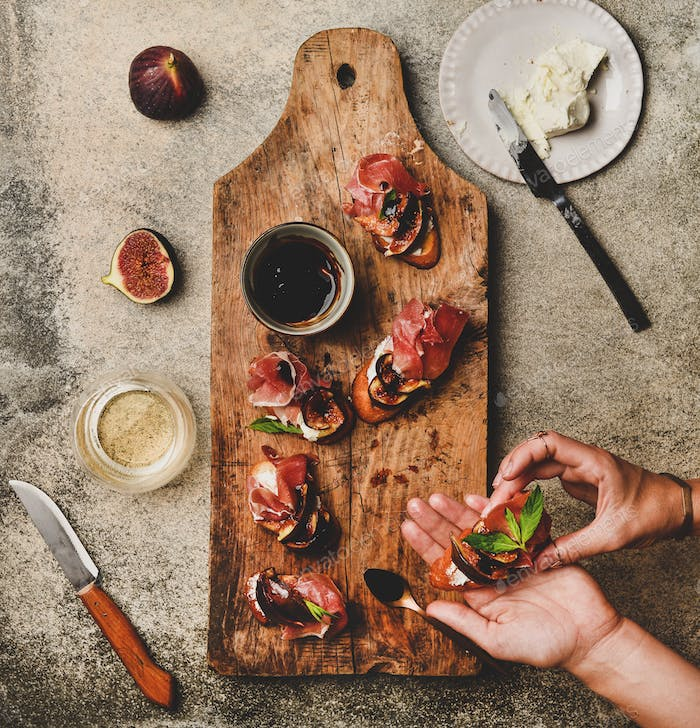 Crostini with prosciutto, cheese and figs and female hands