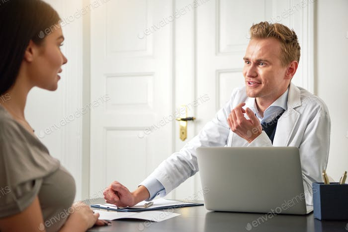 Cheerful male cosmetologist consulting woman at laptop in salon