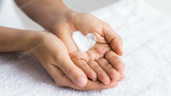 Liebe deinen Körper. Weibliche Hände mit Creme in Herzform