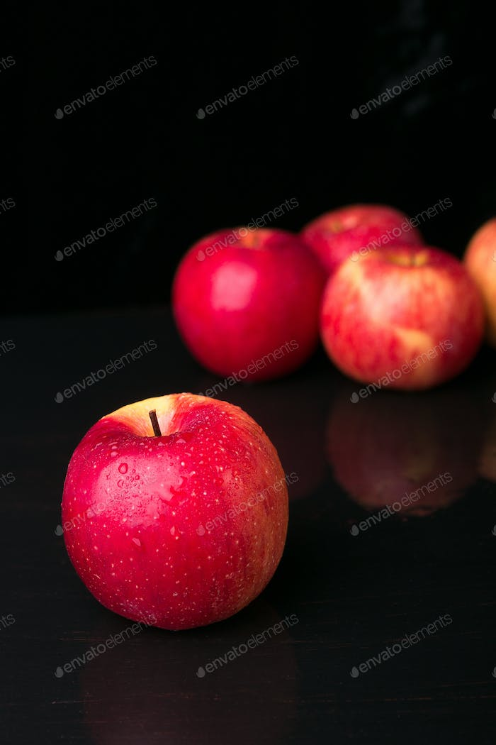 Red apples on black background