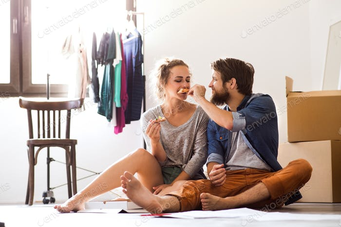 Young couple sitting on the floor moving in new house.