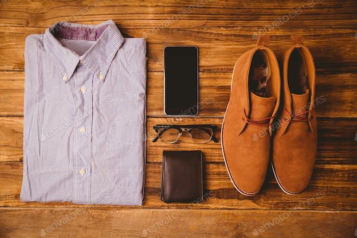 Shirt Schuhe Brille neben Geldbörse und Smartphone auf Holztisch