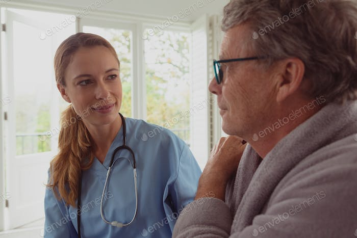 Front view of beautiful Caucasian female doctor consoling active senior man in a comfortable home