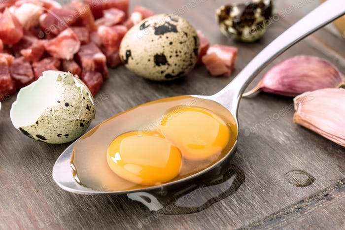 Raw eggs and open quail in metal spoon, on rustic wood