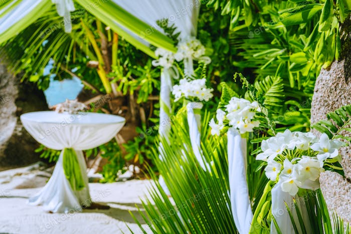 Decorated romantic wedding celebration location, table and chairs on tropical beach. Lush green