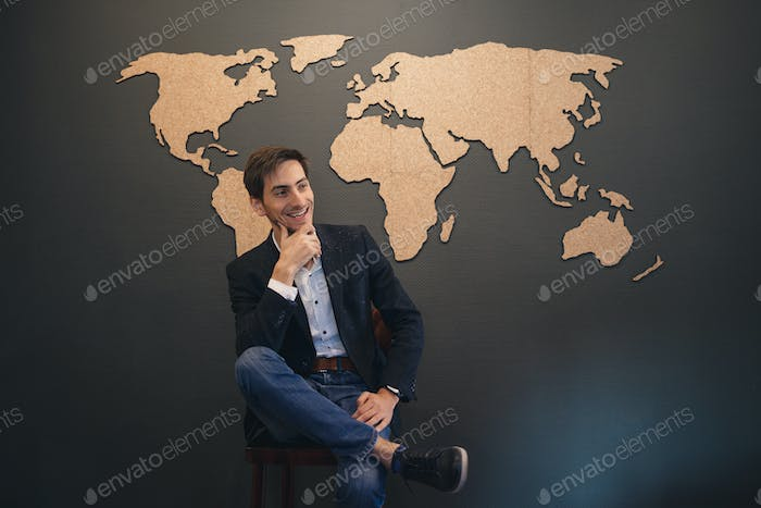 Young man looking to world map with crossed hands