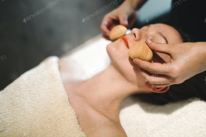 Masseur massaging face with heated objects