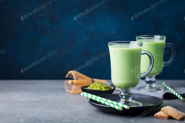 Matcha Green Tea Latte with Matcha Powder and Bamboo Whisk. Grey Stone Background. Copy Space