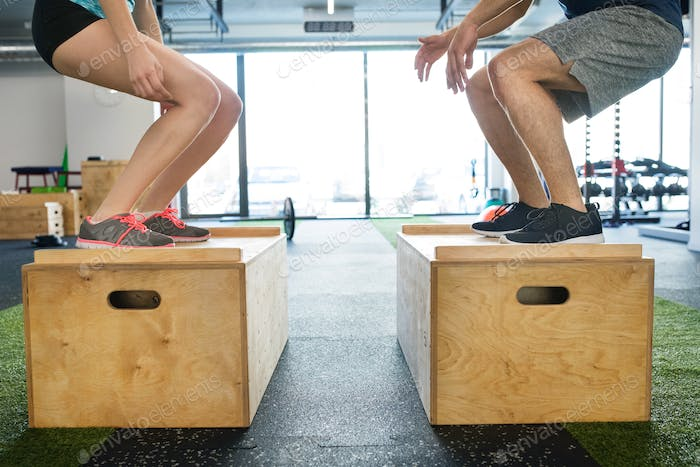 Unrecognizable young fit couple in gym doing box jumps.
