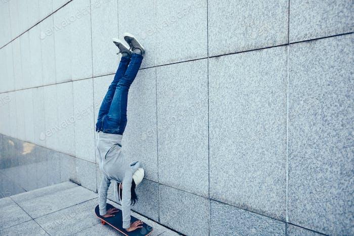 Hipster handstand on skateboarder