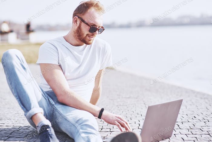 Young man sitting with laptop outside the office. Student learning online. Summer sunny day