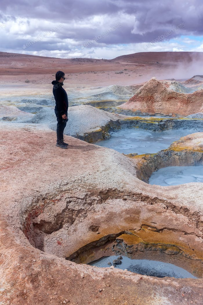 Man standing in front of some mud pits with volcanic activity in the Andean Highlands
