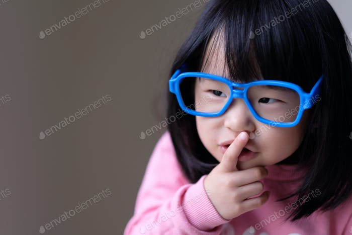 Funny little child with big blue glasses
