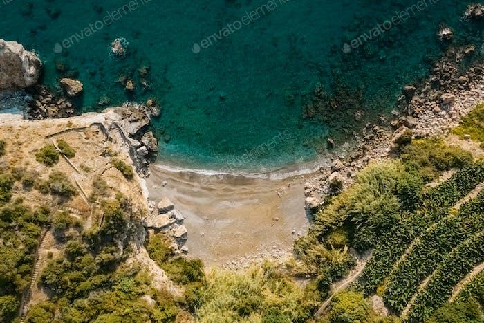 Luftaufnahme von oben auf das Meer trifft felsige Ufer mit grünen Bäumen