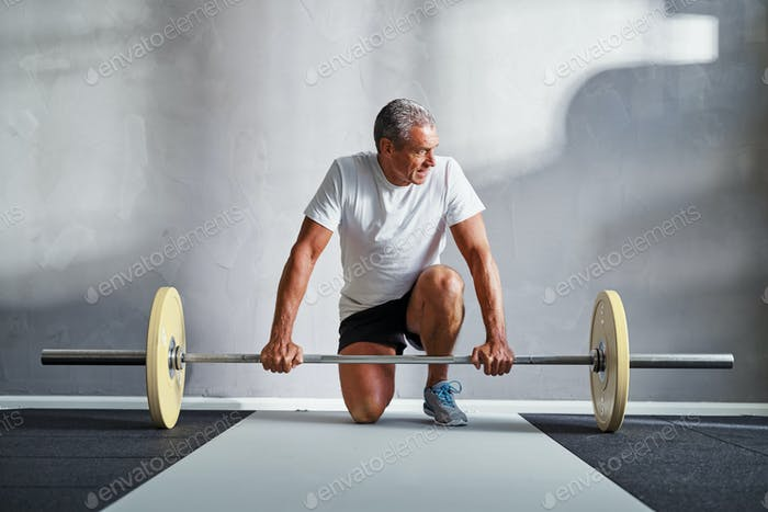 Senior man exercising with weights at the gym