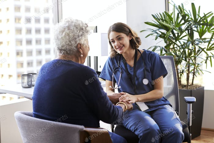 Nurse Wearing Scrubs In Office Reassuring Senior Female Patient And Holding Her Hands