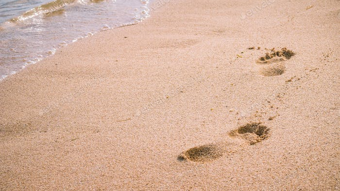 Wave and footprints on clear sandy beach