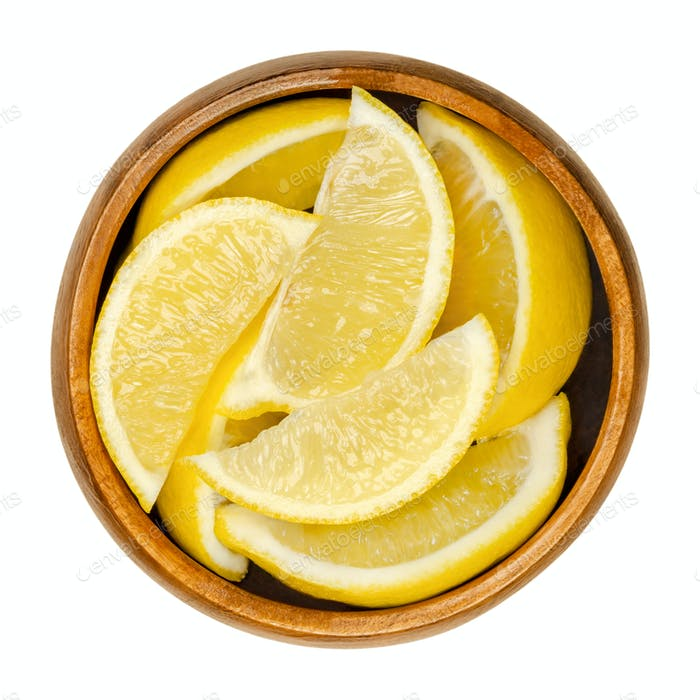 Lemon wedges, freshly cut ripe yellow citrus fruit in wooden bowl