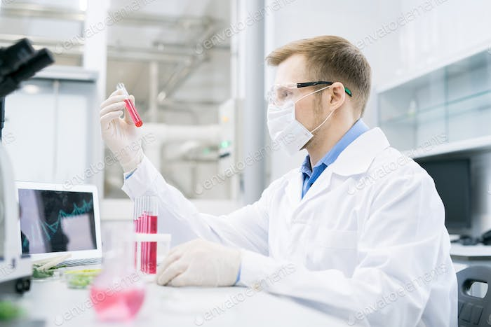 Scientist looking at test tube with solution