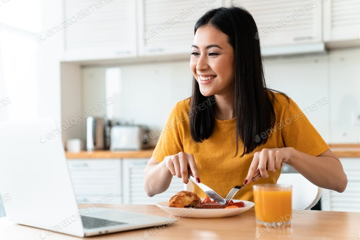 Cheerful young woman using laptop computer have a dinner.